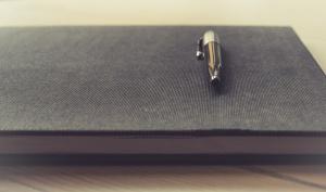 Pen on Black Notebook on Desk