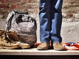 Soldier's Feet and Camo Bag against Concrete Wall