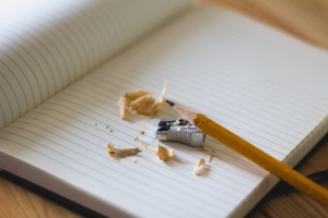 Yellow Pencil with hand Sharpener and Shavings on Notebook