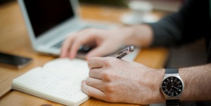 Man jotting down in journal pages